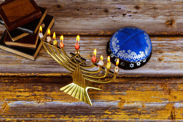 Hanukkah celebration with menorah with wooden dreidels and candles