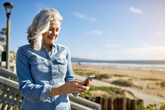 Smiling senior woman using smart phone while standing at Manhattan Beach against sky on sunny day