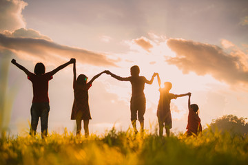 The silhouette of the children holding hands, enjoying the sunset, a group of friends cheering and arms raised in the orange sky and the mountains behind Friendship concept