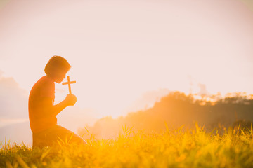 The silhouette of a woman's hand, praying spiritually over the sun, shining with a beautiful blurred sunset backdrop. Is a belief in the Christian concept: Wall mural