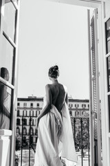 A girl resting at the hotel stands in the opening of an open balcony, wrapped in a sheet. The naked back is turned to the camera, photo black and white