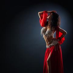 beautiful black-haired girl in red ethnic dress dancing oriental dances in the dark