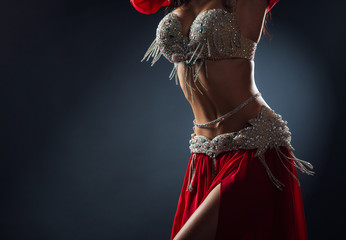 Beautiful belly dance of a girl in a red decorated ethnic dress in dark