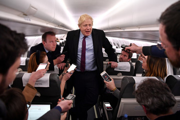 Britain's Prime Minister and Conservative leader Boris Johnson talks with journalists as he travels aboard a plane bound for Birmingham