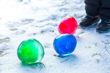 child plays a frozen ball