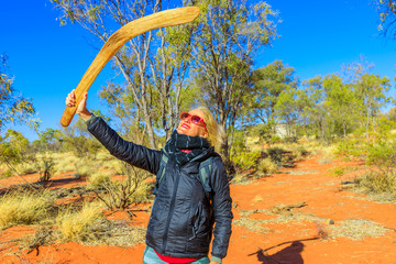 Happy tourist woman holding an aboriginal weapon of boomerang used by Luritja and Pertame people in Central Australia, Northern Territory, Australia, Pacific