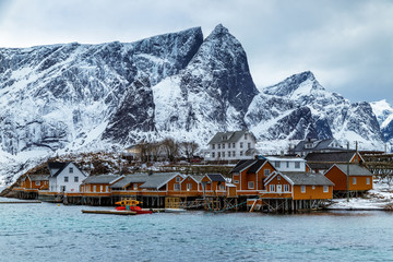 Beautiful winter landscape on Lofoten islands with traditional fishing village, yellow rorbu houses and mountains. Blue hour. Travel Norway.