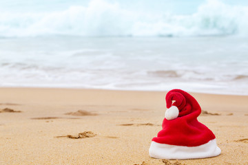 Santa Claus hat on the sandy ocean