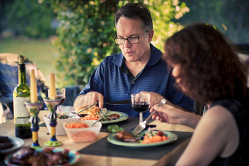 Mature man and woman having lunch together at table in yard