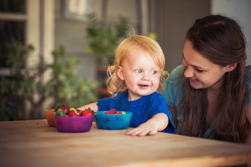 Happy young woman looking at cute son with strawberry bowls at table