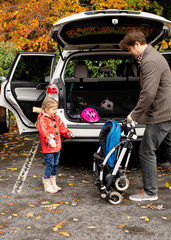 Daughter looking at father with stroller by car trunk at park