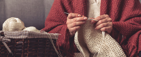 Knitting.Crocheting a hobby and lifestyle, Woman's hands knit from light yarn at home, mood, comfort, zero waste, handmade,lagom hugge cozy,long banner Wall mural