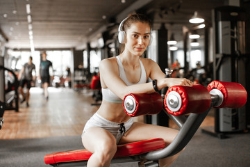 Poster Ontspanning Close up portrait of young pretty european fitness woman at the gym and listen music in headphones. Breaking relax while exercise workout. Concept of health and sport lifestyle. Athletic Body...