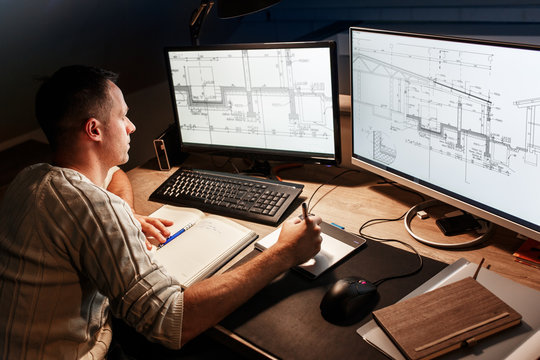 Engineer  working at home.He using digital pen and examining blueprint on screen.