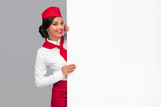 Cheerful air hostess peeking out from behind blank banner