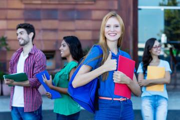 Studentin mit roten Haaren vor der Uni
