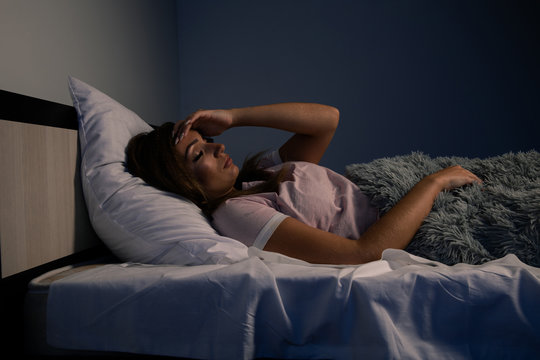 Stressed female insomnia. Young lady lying in the bed and want to sleep