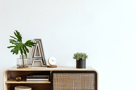 Interior design of living room at scandinavian apartment with stylish commode, plant, tropical leaf, books, big letter, white clock and elegant accessories. Modern home decor. Template. Copy space.