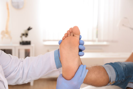 Male orthopedist checking patient's foot in clinic, closeup