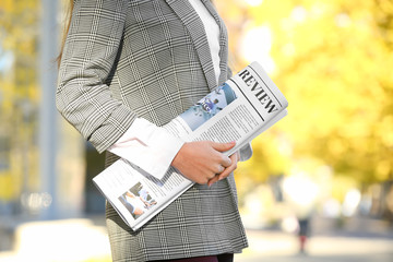 Young businesswoman with newspaper outdoors