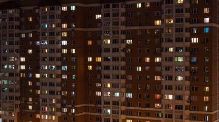 Glowing apartment building windows at night. Outdoor view of living house facade with warm illumination light. Architecture, urban concept Wall mural