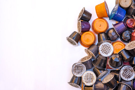 Used coffee capsules of various colors and flavors. These capsules are a problem because they are expensive and difficult to recycle.