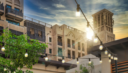 composited image design with festive lighting and sunset over classic Arabian styled architecture postmodern