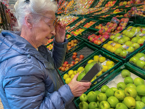 Senior woman buying vegetables in the supermarket