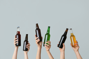 Poster Alcohol Hands with bottles of beer on grey background