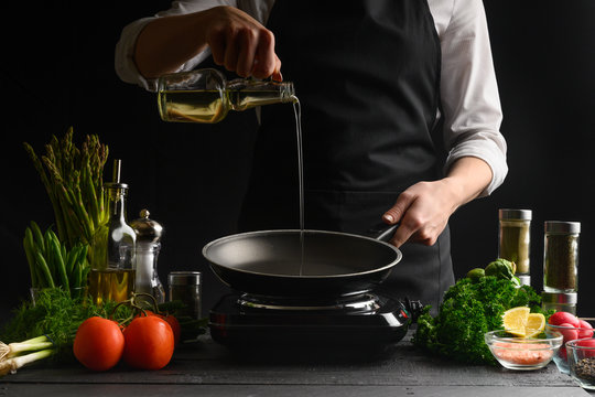 Chef pouring oil on a frying pan, freezing in motion. On a background with ingredients. Homemade fish recipes, gastronomy