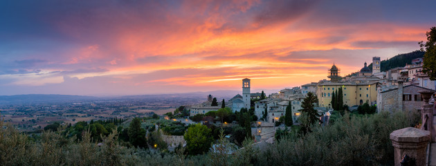 Sunset over Assisi, Umbria, Italy. Monumental, historic and romantic Italian countryside with roads, houses, churches. Skyline cityscape Assisi with hills of Umbria Fotomurales