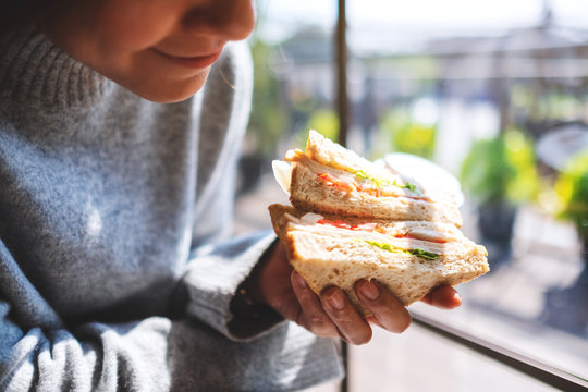 Closeup image of a woman holding and eating whole wheat sandwich in the morning