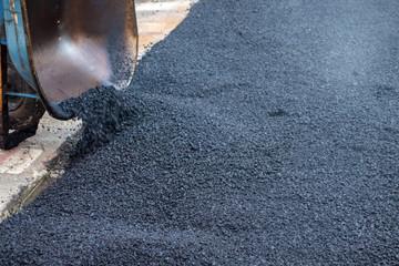 Urban city street black top, tarmac, asphalt patch up work and repairs wheelbarrow.