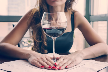 Foto op Plexiglas Alcohol Closeup portrait of young female customer drinking red wine with eyes closed. Woman drinking wine, taking a SIP from a glass glass. Wine tasting in restaurant.