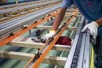 The technician cleaning conveyor belt in production line at factory plant