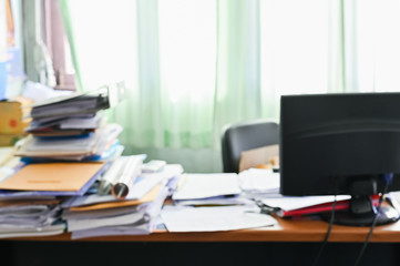 Blurred of Cluttered desk, full of documents A mess desk with many working stuff