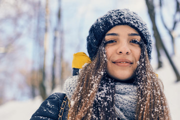 Winter portrait of young beautiful woman wearing knitted snood covered in snow. Snowing winter beauty fashion concept Wall mural