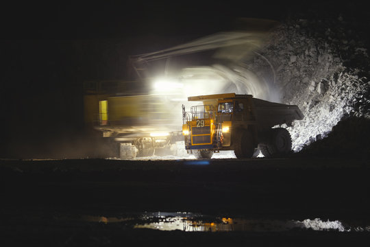 Blurry image of the excavator in motion on a long exposure loading stone ore into the body of a mining dump truck, on a dark background with artificial illumination at night.