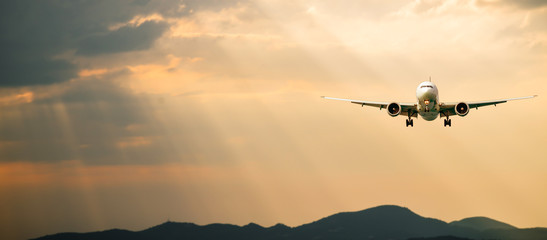 Passenger airplane. Landscape with Front of white airplane is flying in the orange sky with clouds over mountains, sea at colorful sunset. Passenger aircraft is landing. Commercial plane. Private jet Fotobehang