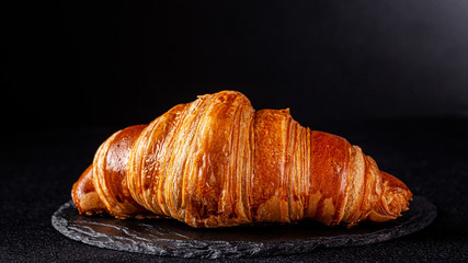 French cuisine concept. French croissant from puff pastry dough lies on a black slate board, on a black background. copy space Fototapete