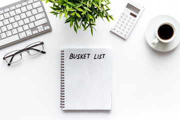 Bucket list. Blank notebook to write goals and wishes on white office desk top-down