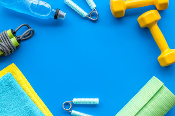 Gym equipment - dumbbells, jump rope - frame on blue background top-down copy space