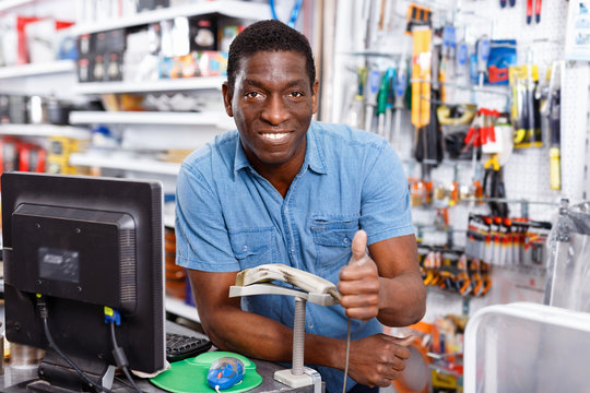 Portrait of happy successful owner of household goods store standing behind counter, giving thumbs up