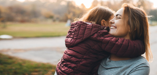 Lovely little girl embracing her mother while mother is laughing and holding on the arms he daughter against sunset outdoor.