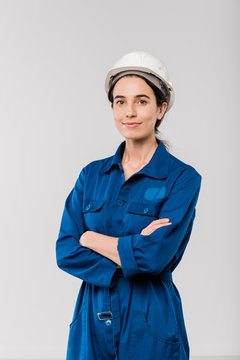 Pretty young cross-armed female engineer in blue workwear and safety helmet