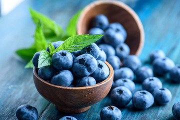 Bowl of fresh blueberries on blue rustic wooden table closeup. Fotobehang