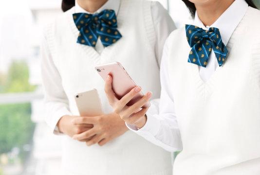 スマートフォンを持つ女子学生の手元