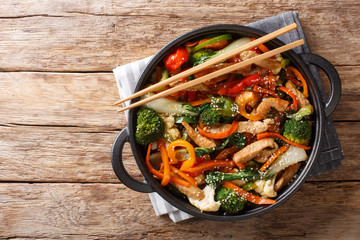 Chinese cuisine stir fry pork with vegetables and sesame seeds close-up in a pan. Horizontal top view