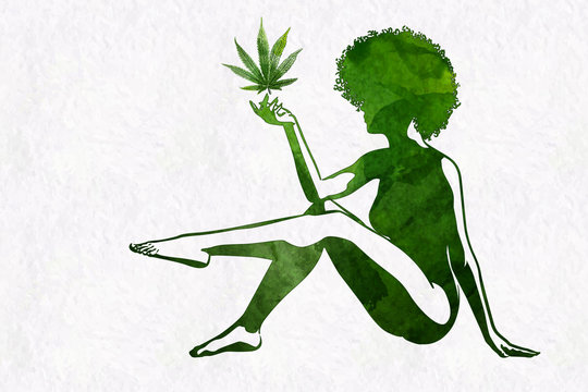 Woman's silhouette with afro hairstyle holding marijhuana leaf in her hand