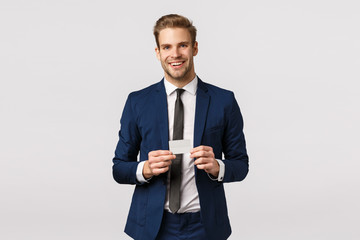 Handsome, successful young businessman in classic blue suit, holding credit card and smiling joyfully, promote bank, online purchase system, order product, got platinum card showing it airport staff